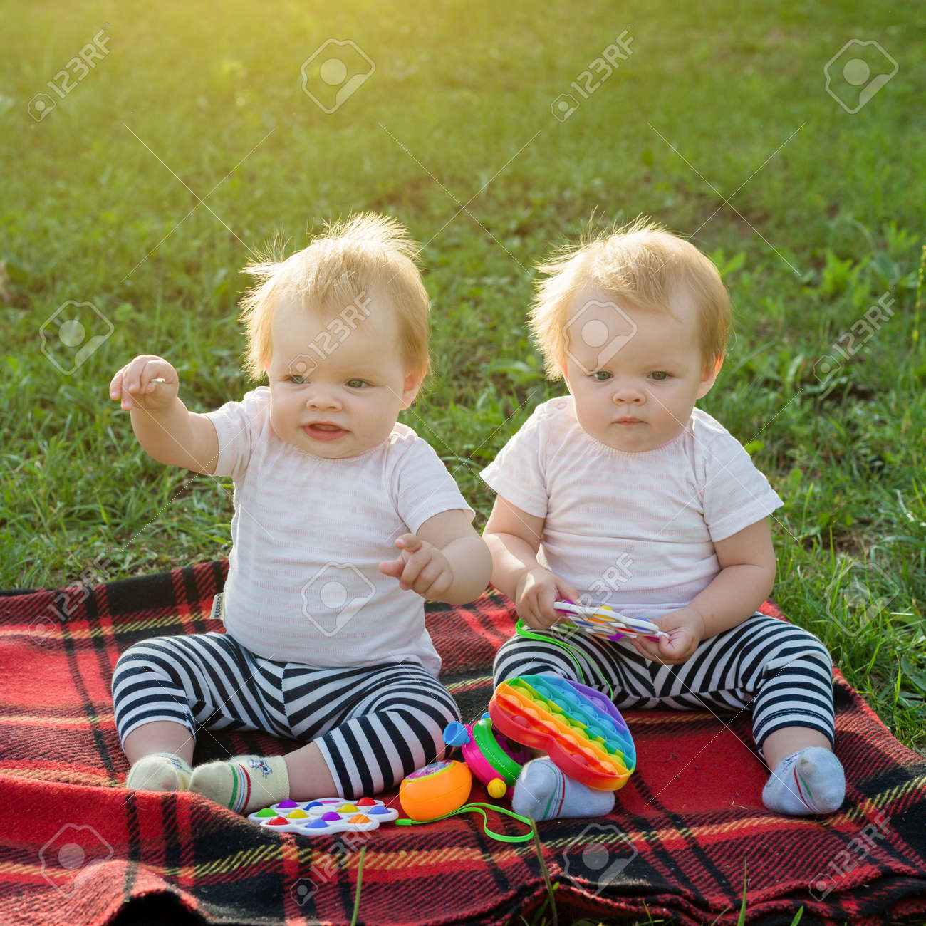Twin girls play with bright toys on blanket in a city park. - 171582700