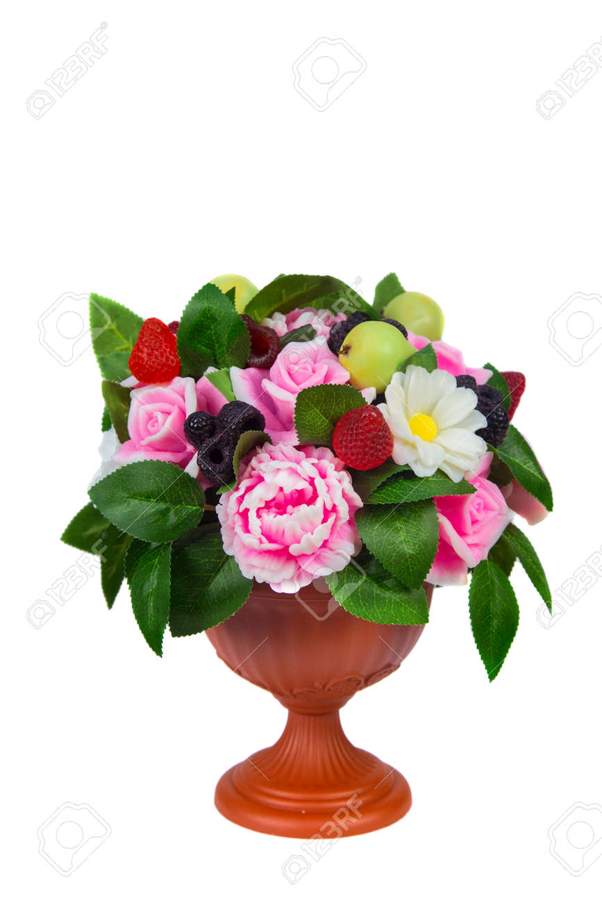 A vase with handmade soap in the shape of flowers raspberries blackberries and pears on a white background. Isolated - 171956013