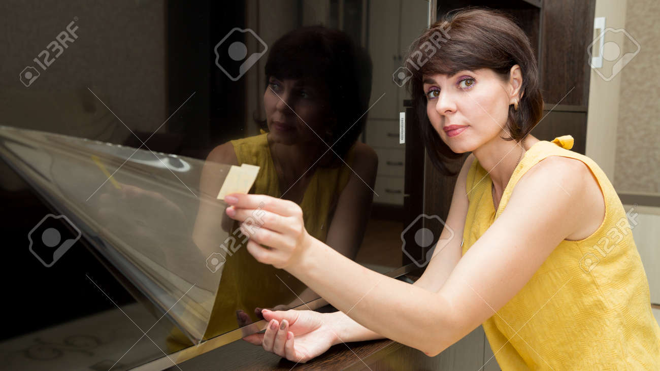 A brunette in a yellow dress in apartment with a smile takes a film from a new large LCD TV. - 171730248