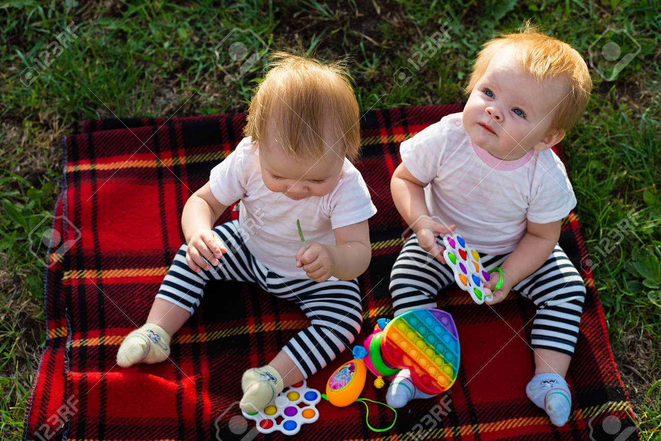 Two twins on a blanket with bright toys look up. - 171759803