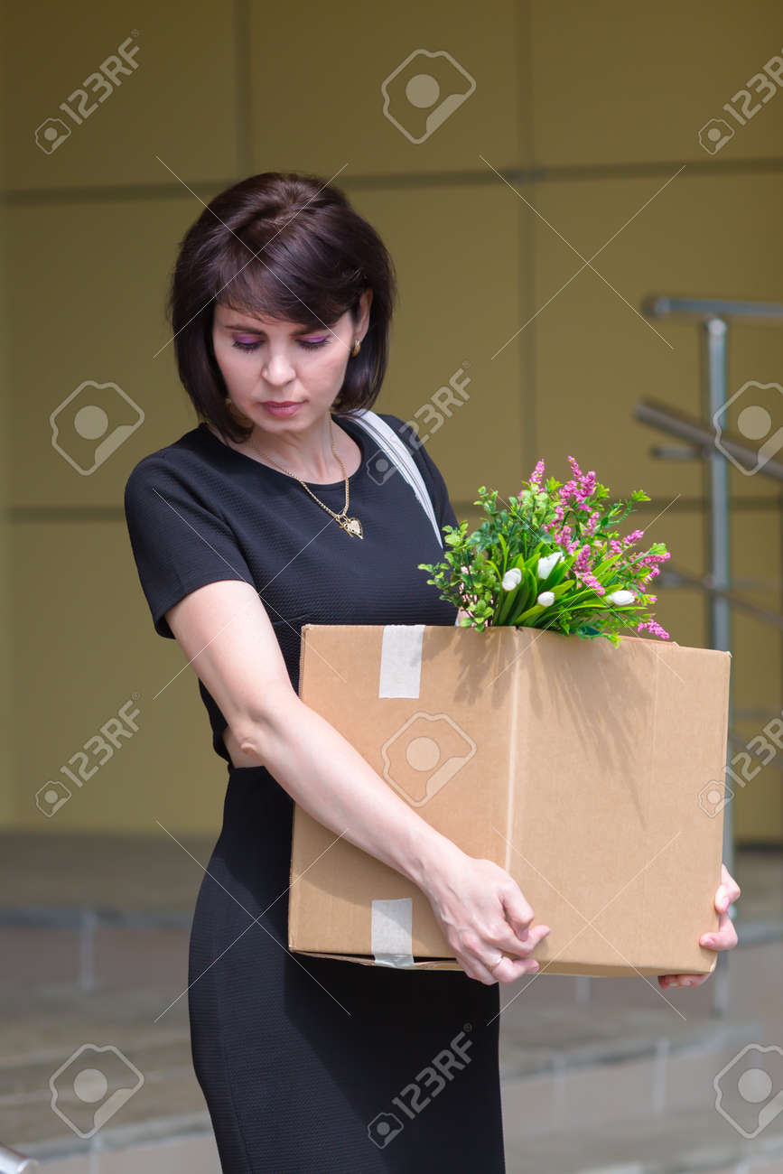 A fired upset brunette lawyer leaves office with a box of personal belongings. - 171802321