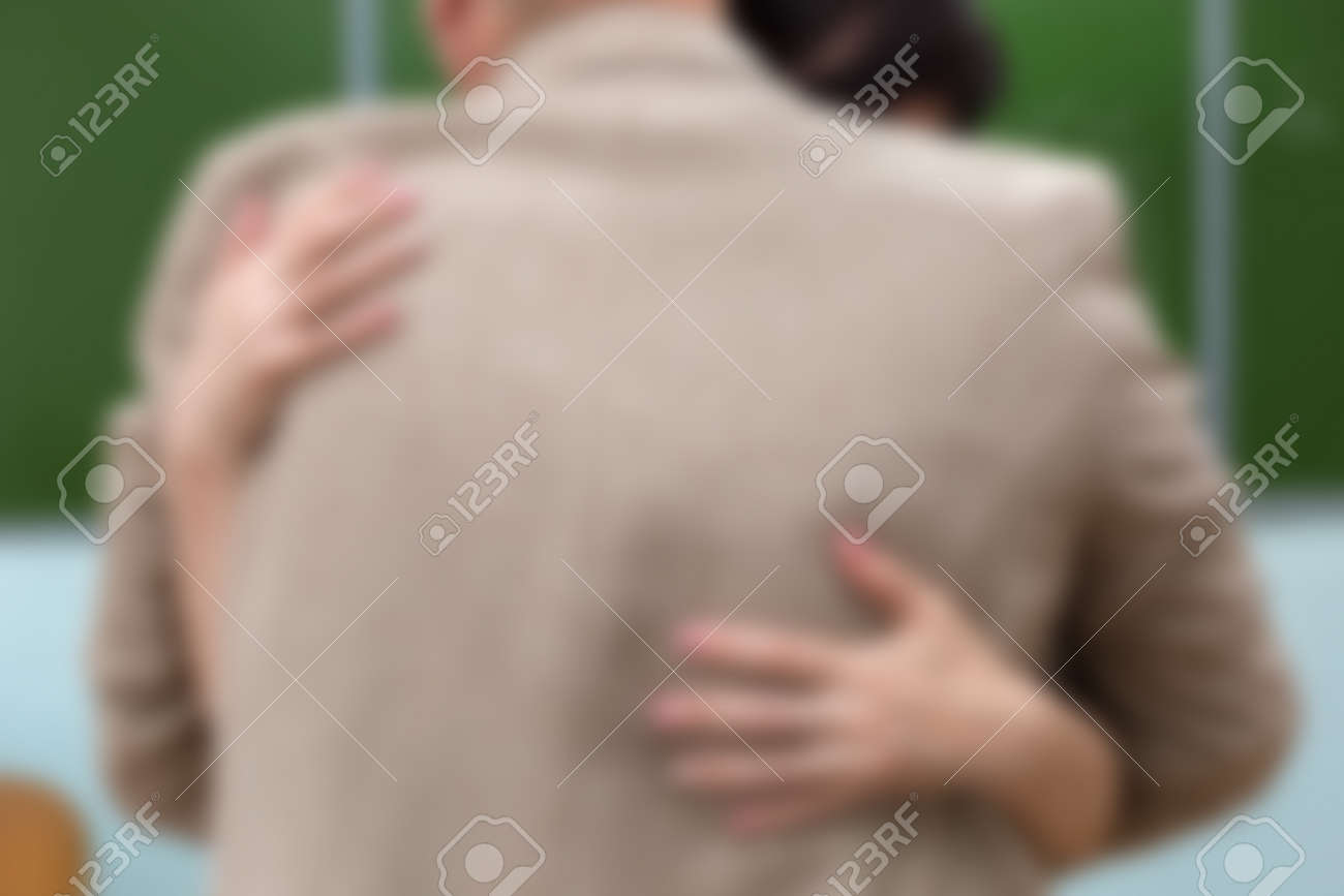 A man and a woman embrace in a school classroom at the blackboard. Blurred, no focus - 171840312