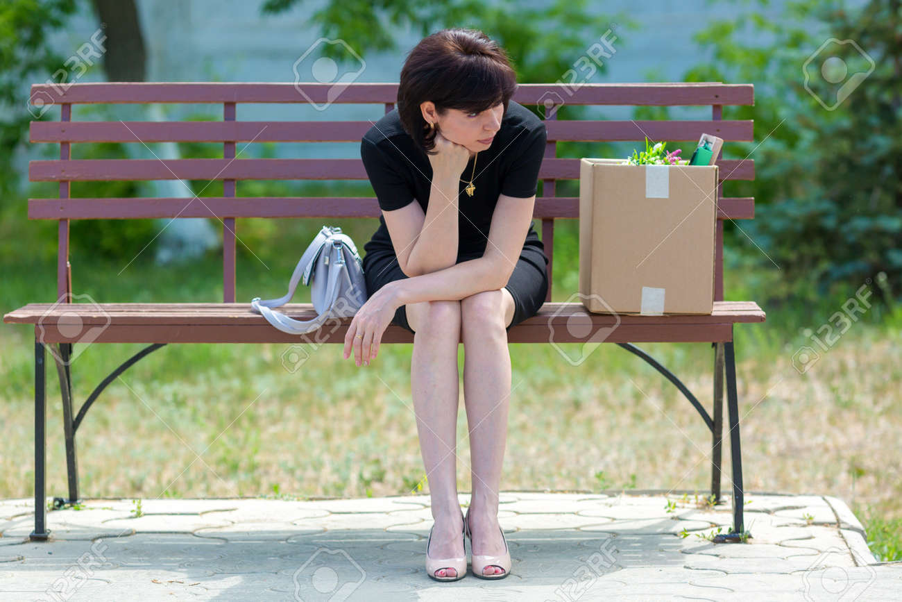 A frustrated brunette secretary is sitting on bench with a box of personal belongings. - 171802033