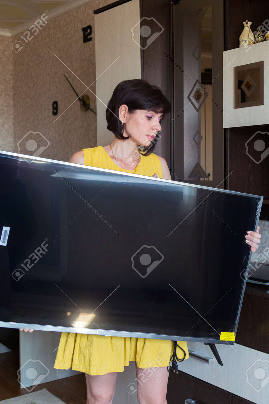 A woman with great difficulty brings new large LCD TV into the apartment. - 171802214