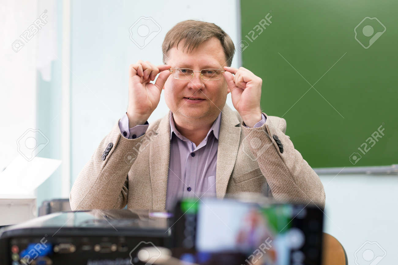 A teacher with glasses 40 years old in a school classroom sits at his desk and conducts a lesson remotely. - 171840322