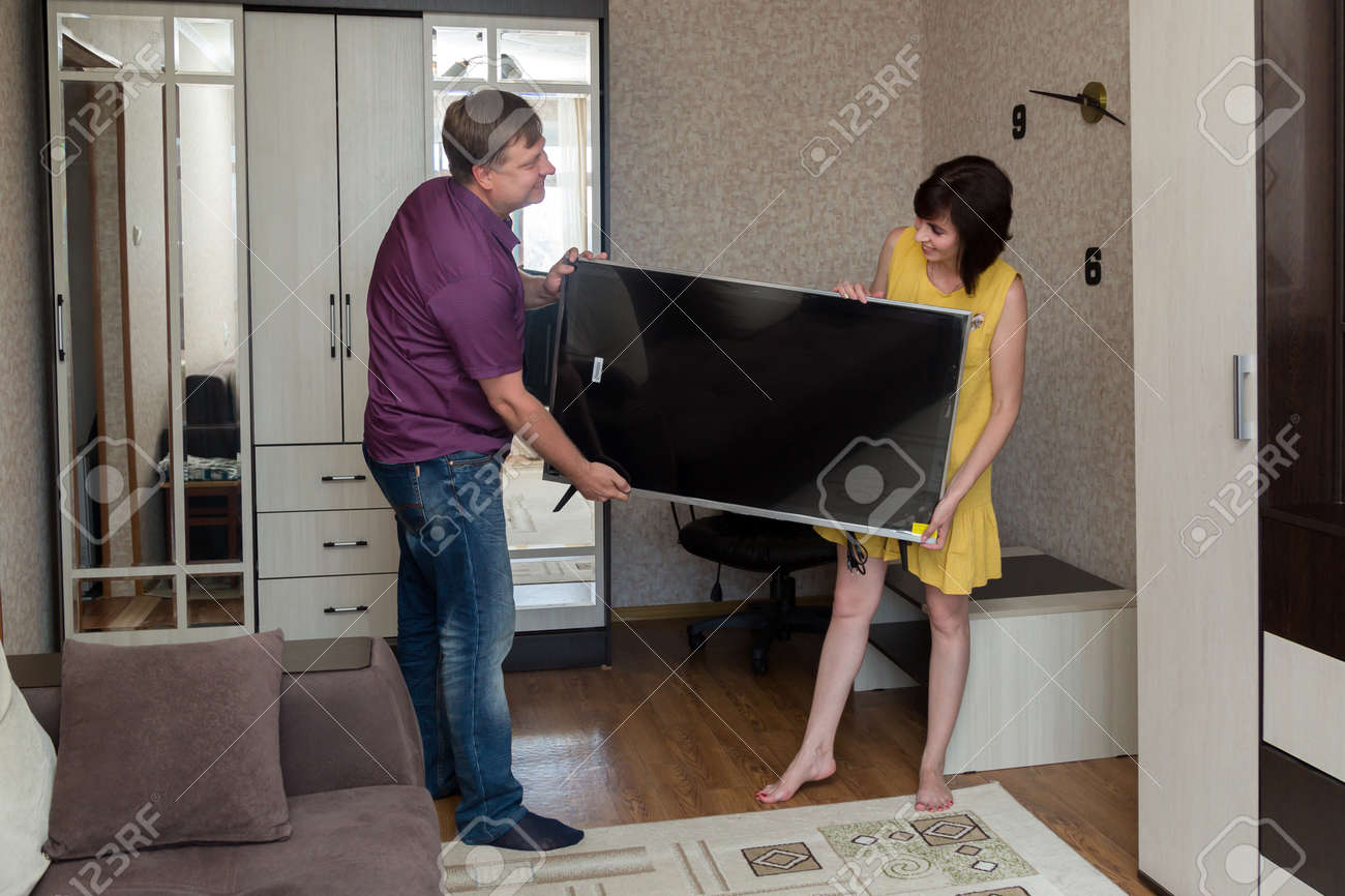 A man and a woman are happy to bring a new large LCD TV into the apartment. - 171840318