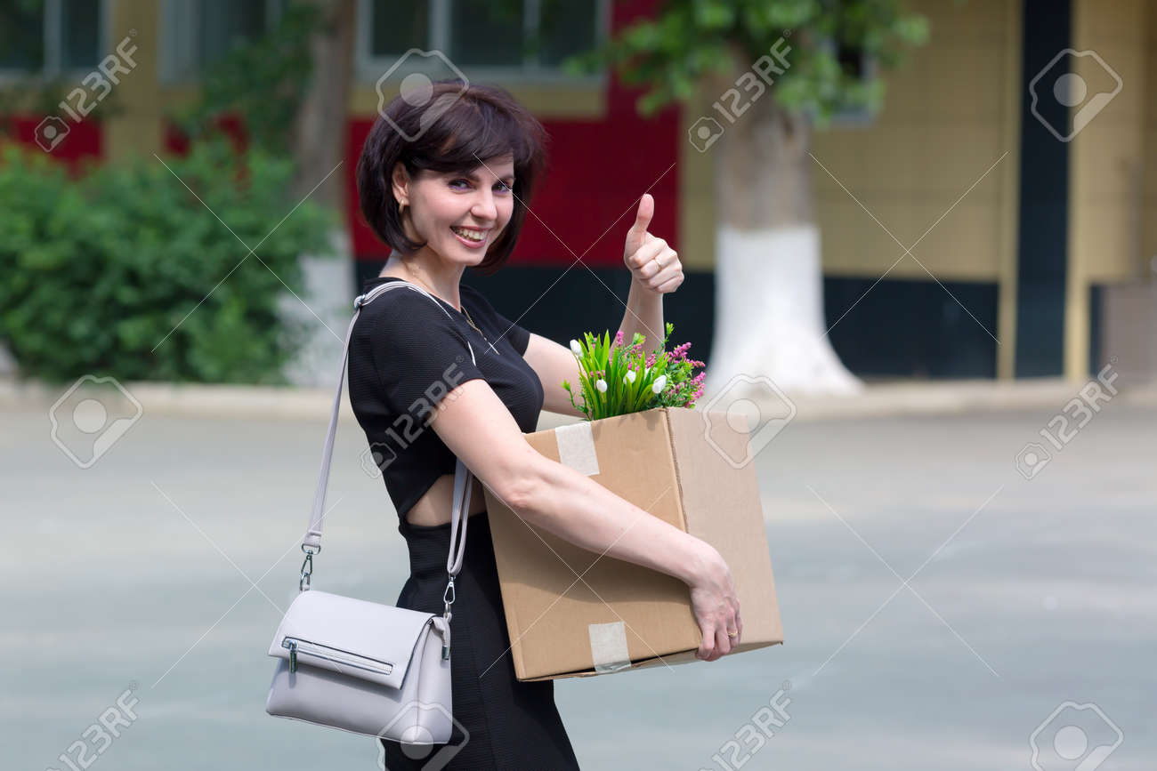 A happy brunette woman with a box of personal belongings shows with a hand gesture that she was hired. - 171840319