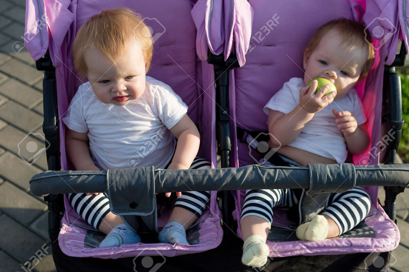 Cute 6 month old children are sitting next to each other in a baby stroller. - 171840323