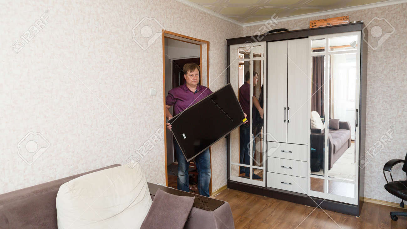 An adult man brings a large new LCD TV into apartment. - 171868908
