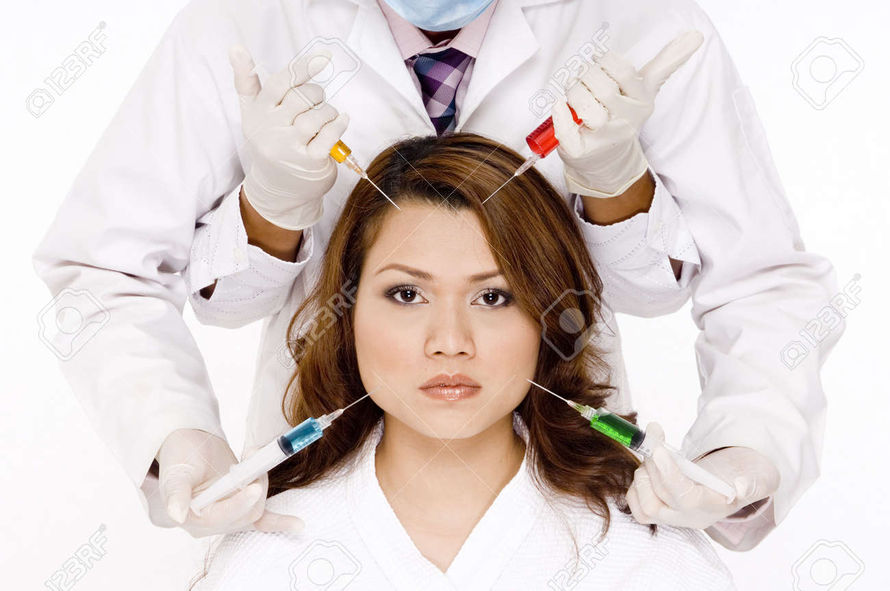 A woman with four hands holding syringes with different colored liquids Stock Photo - 486324