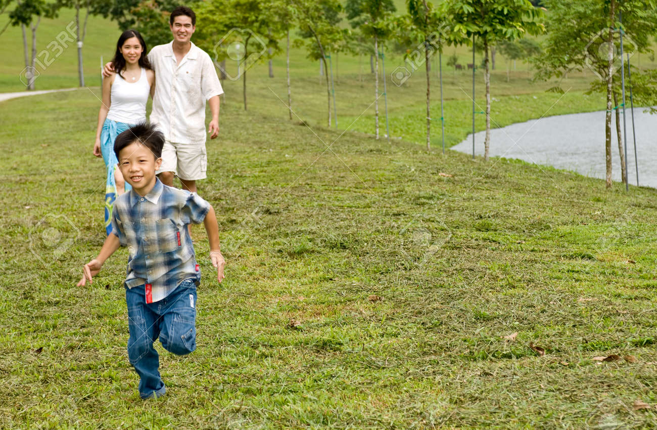A young couple with their young son running by a lake Stock Photo - 1637211