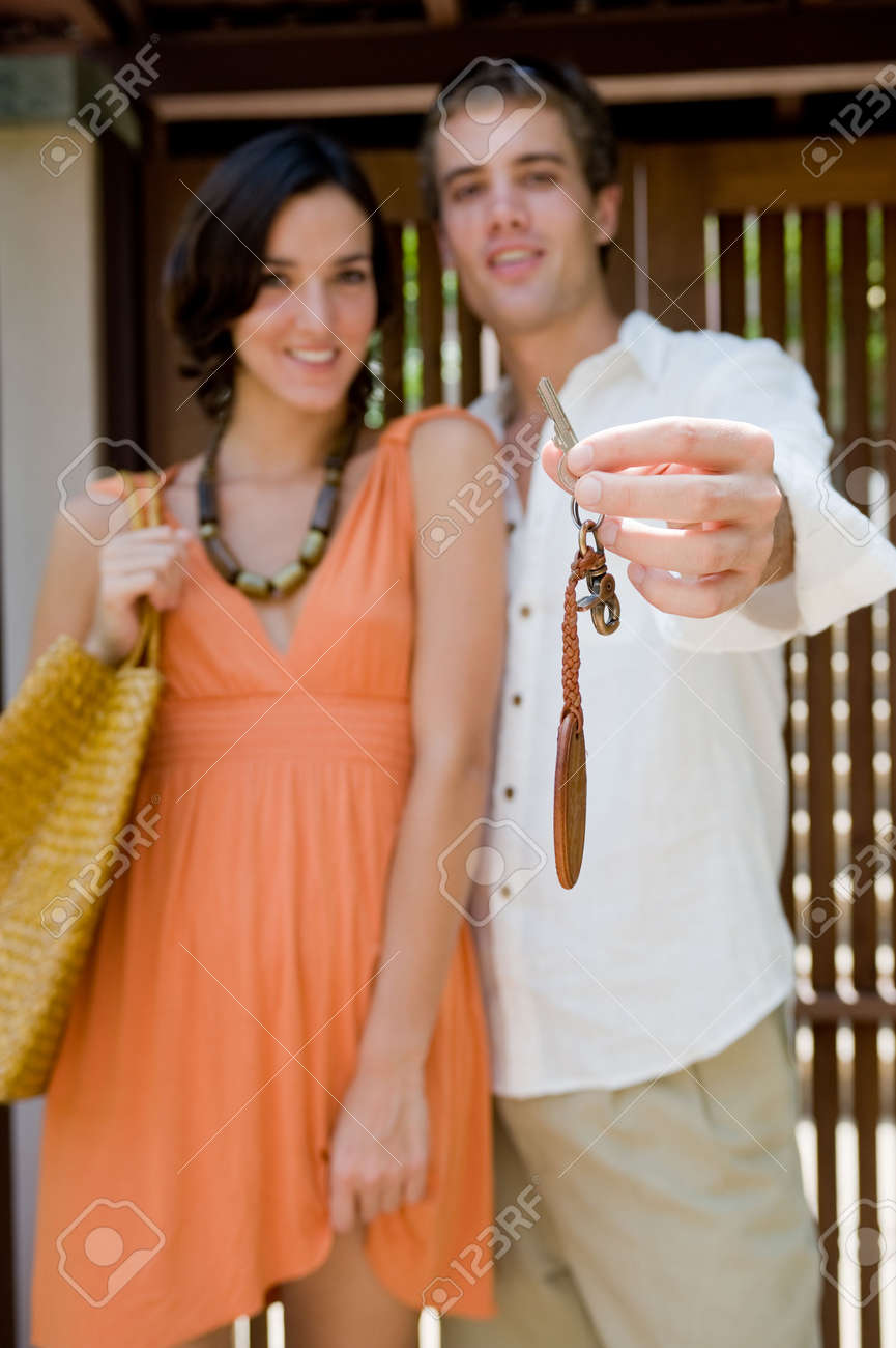 A young couple holding the key to to their home with door behind them (shallow depth of field used) Stock Photo - 2634934