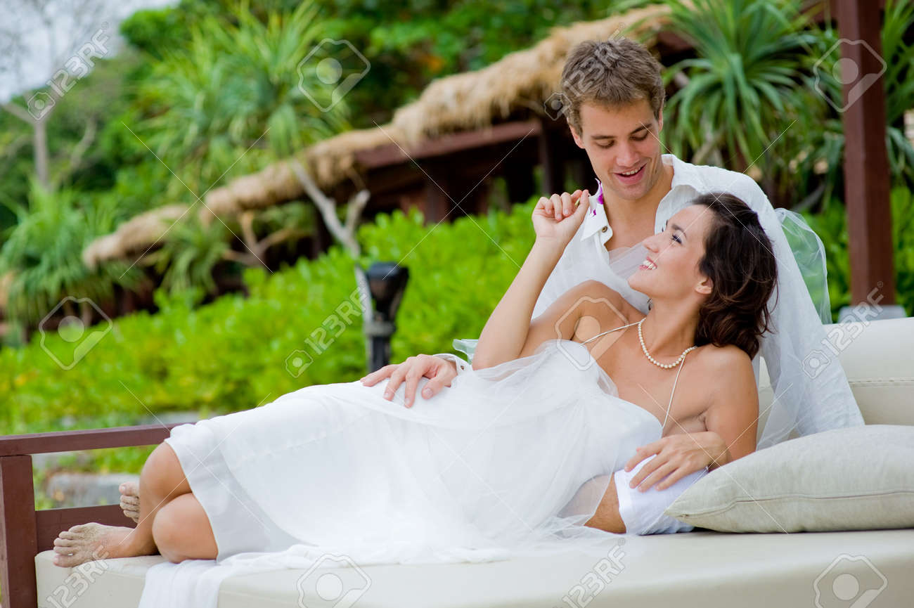 A young bride and groom lying together in an outdoor setting by beach Stock Photo - 2645724