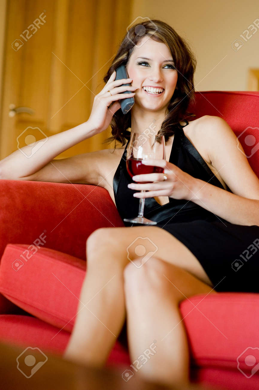A beautiful young woman in black dress sitting on sofa with phone and wine Stock Photo - 3180032
