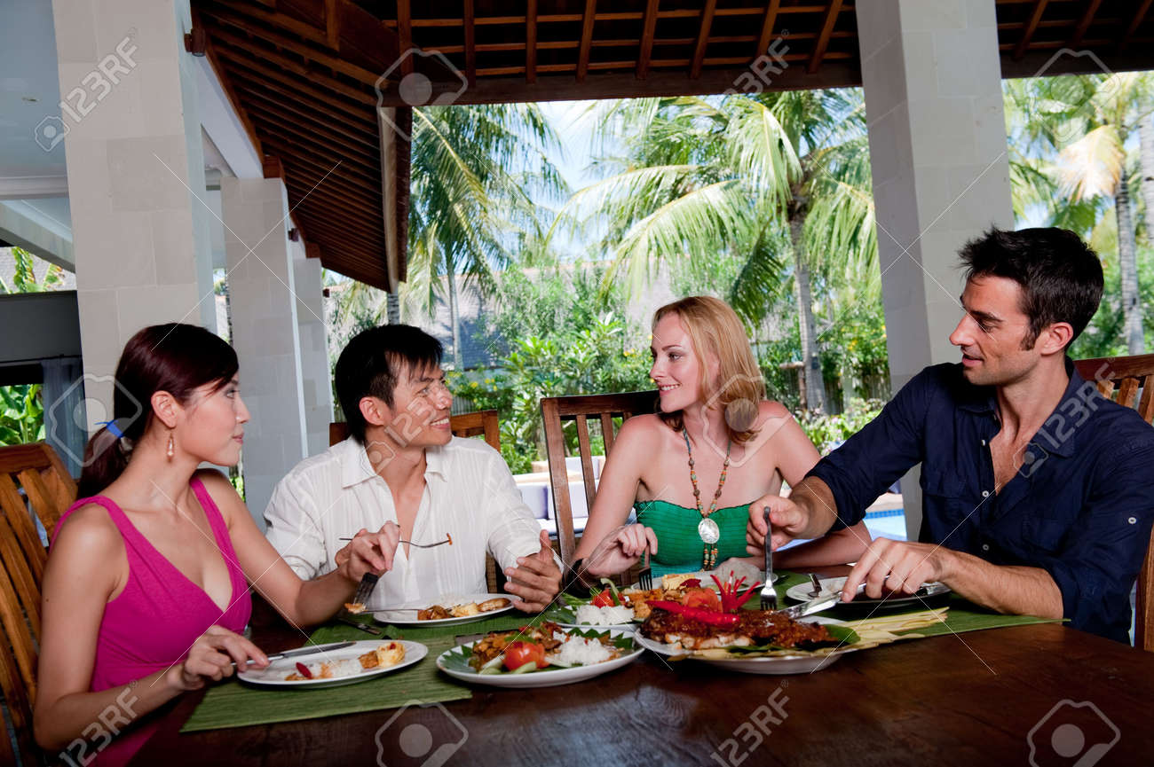 A group of four adults enjoying lunch at their villa on vacation Stock Photo - 4643619