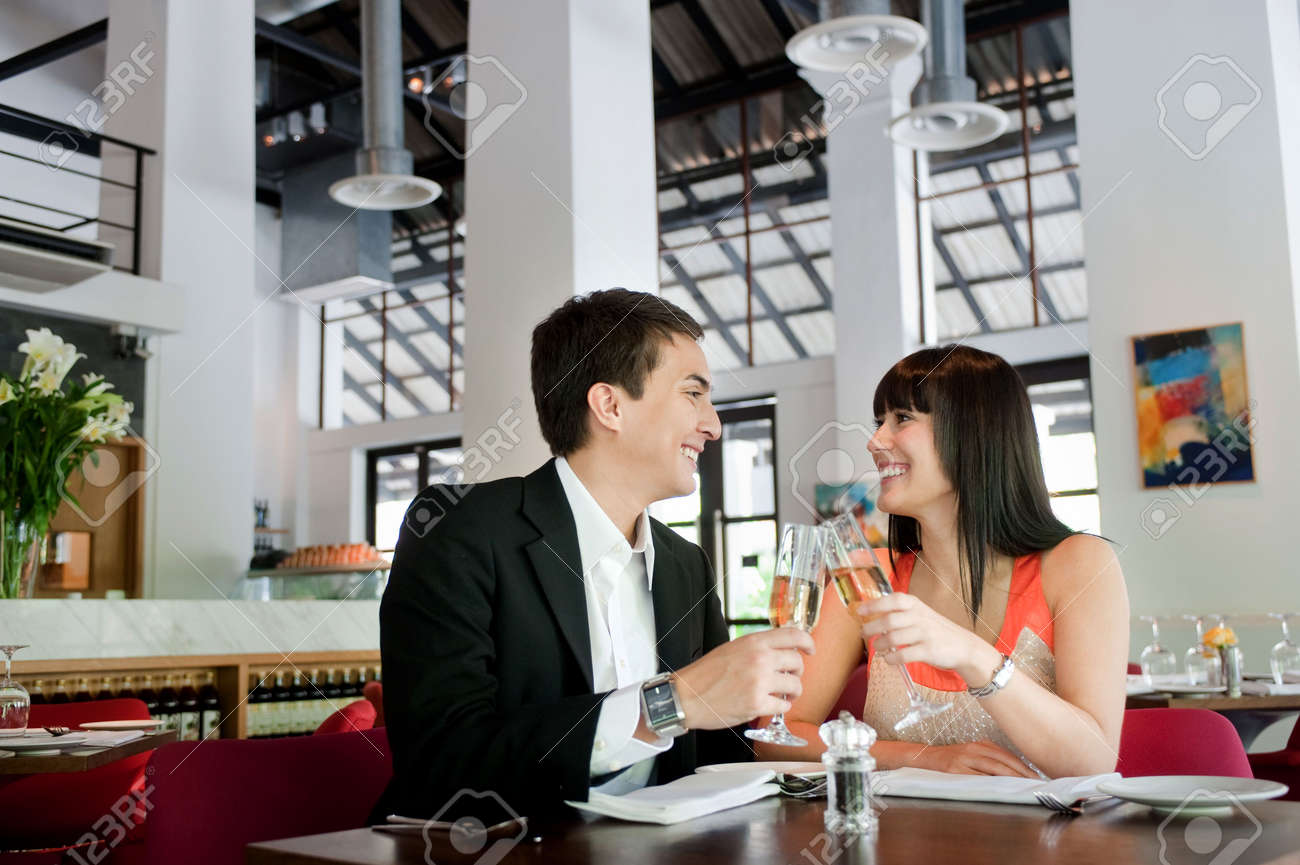 An attractive young couple toasting with white wine in a restaurant Stock Photo - 5341024