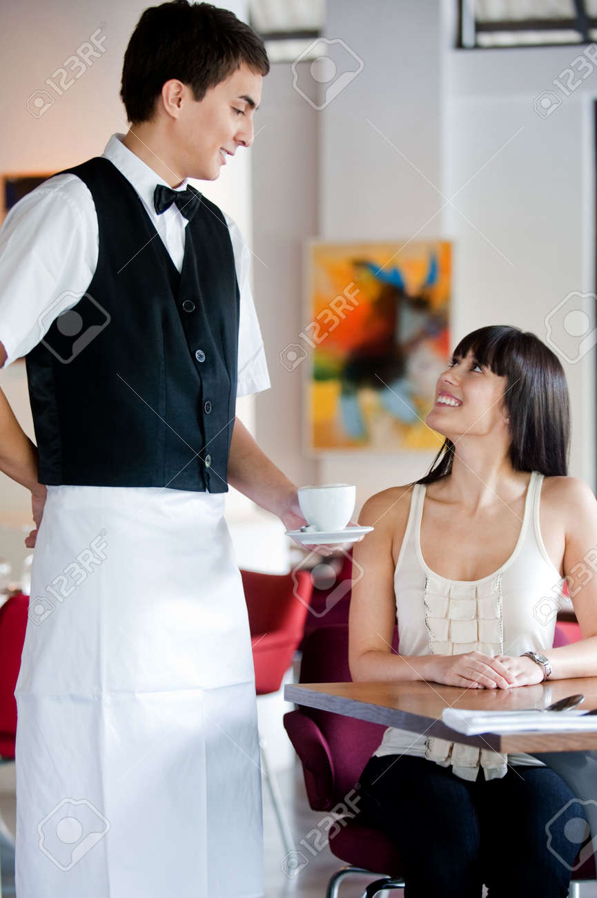A young and attractive waiter serving coffee to a customer in an indoor restaurant Stock Photo - 5341025