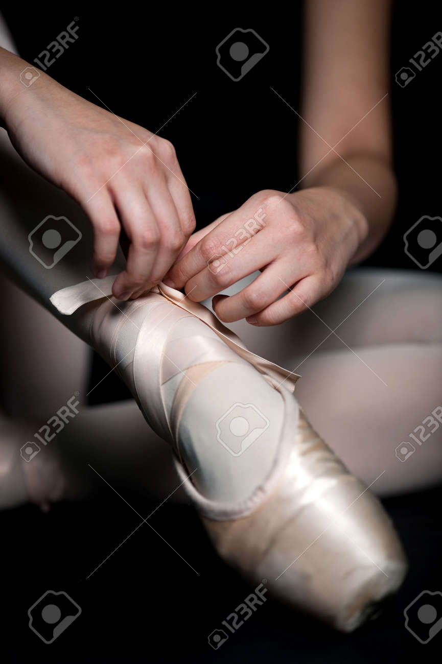 A ballerina tying her ballet slippers on, against black background Stock Photo - 5802553