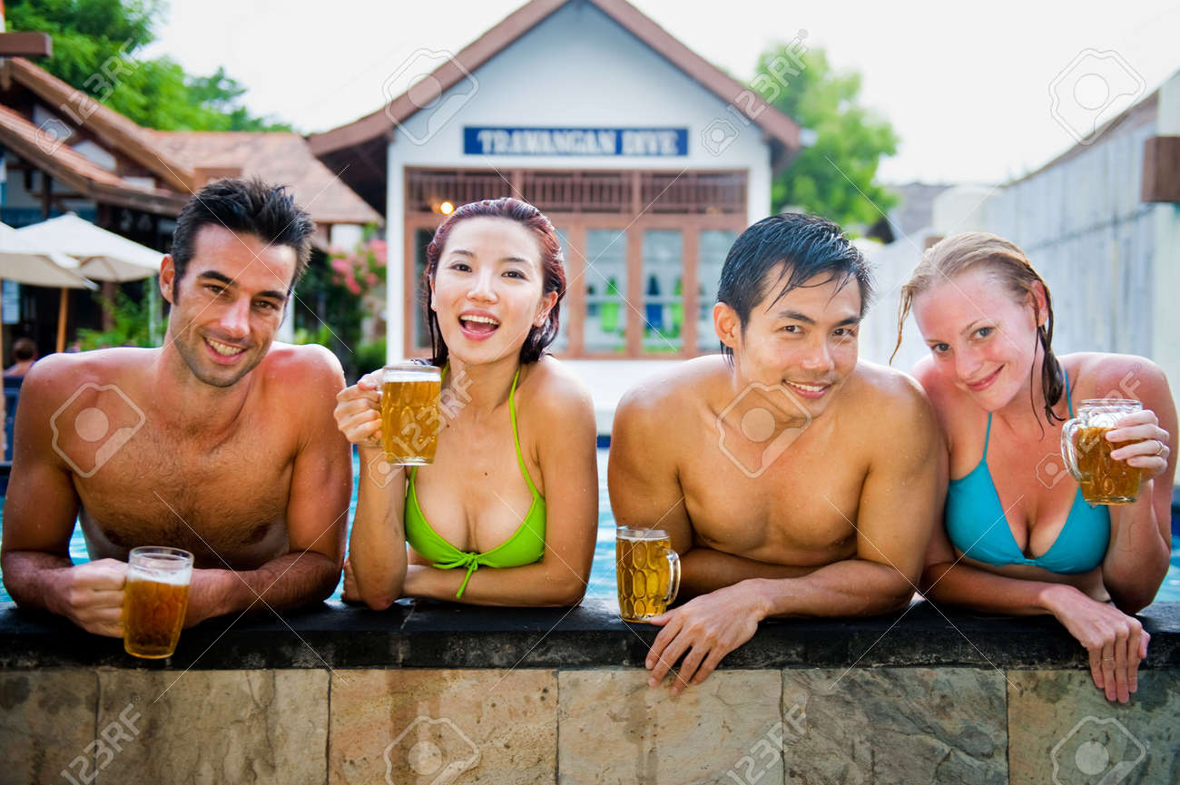 A young attractive Chinese woman drinking a beer in the pool Stock Photo - 5913620