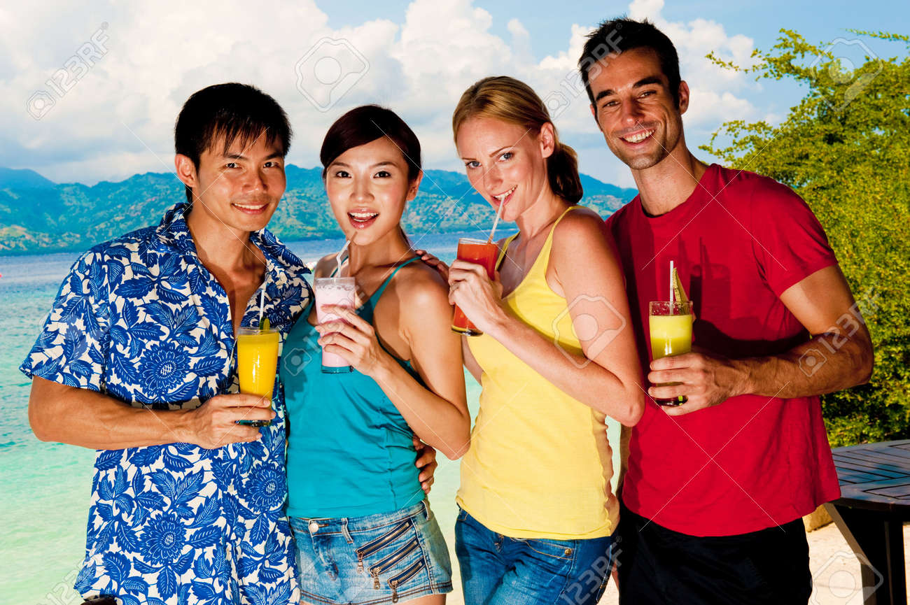 A group of asian and caucasian friends drinking fruit juice by the seaside Stock Photo - 5999847