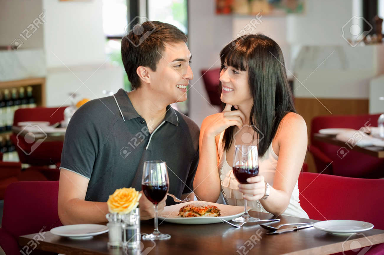 A young and attractive couple dining together in an indoor restaurant Stock Photo - 6101587