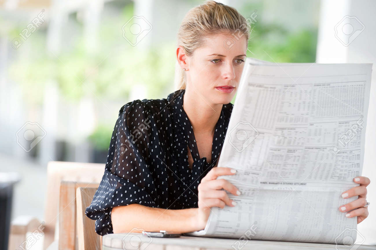 A young attractive woman reading newspapers at a cafeteria - 6338211