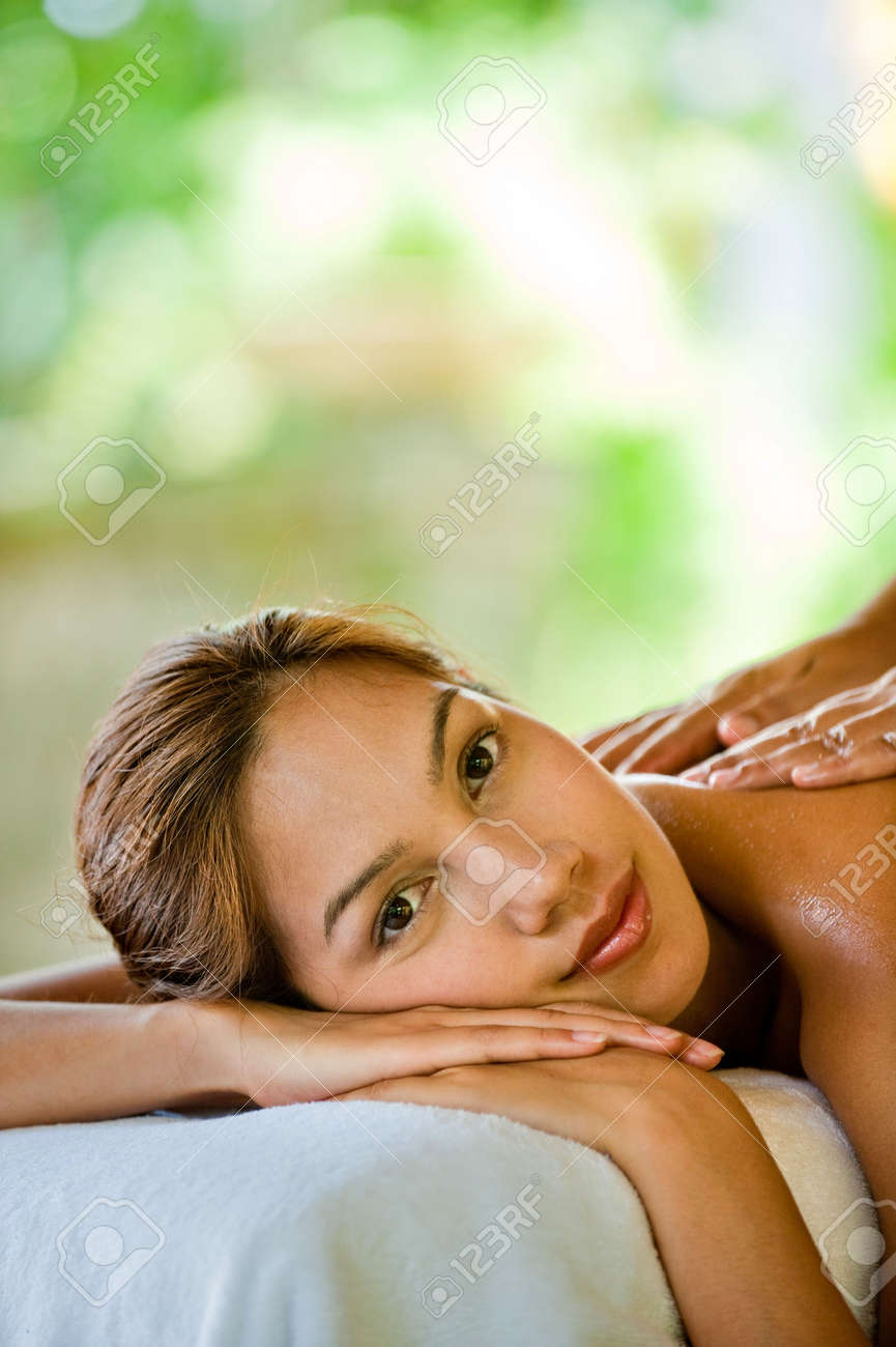 An attractive young woman enjoying a back massage at a spa outdoors Stock Photo - 6672001
