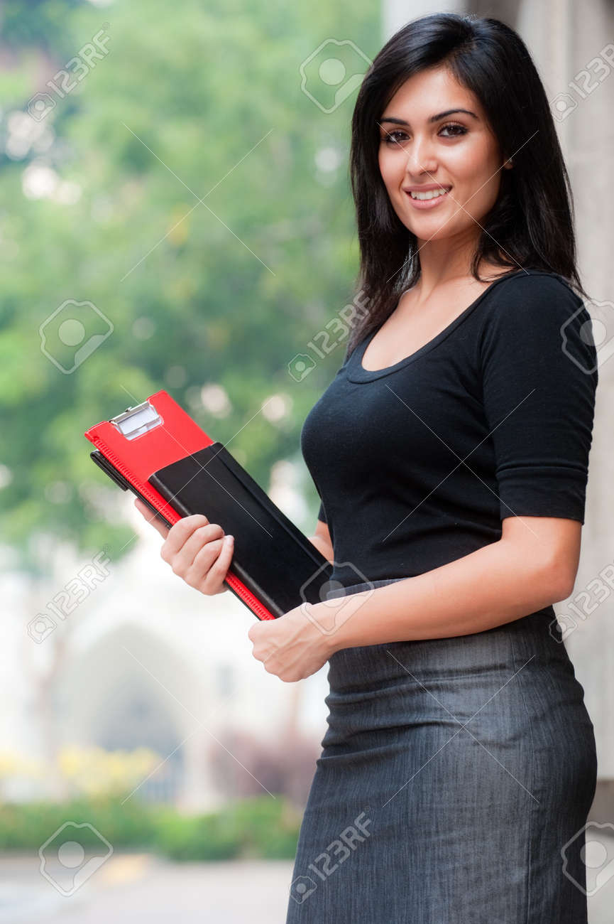 A beautiful young businesswoman standing outside holding files and notebook - 8179088