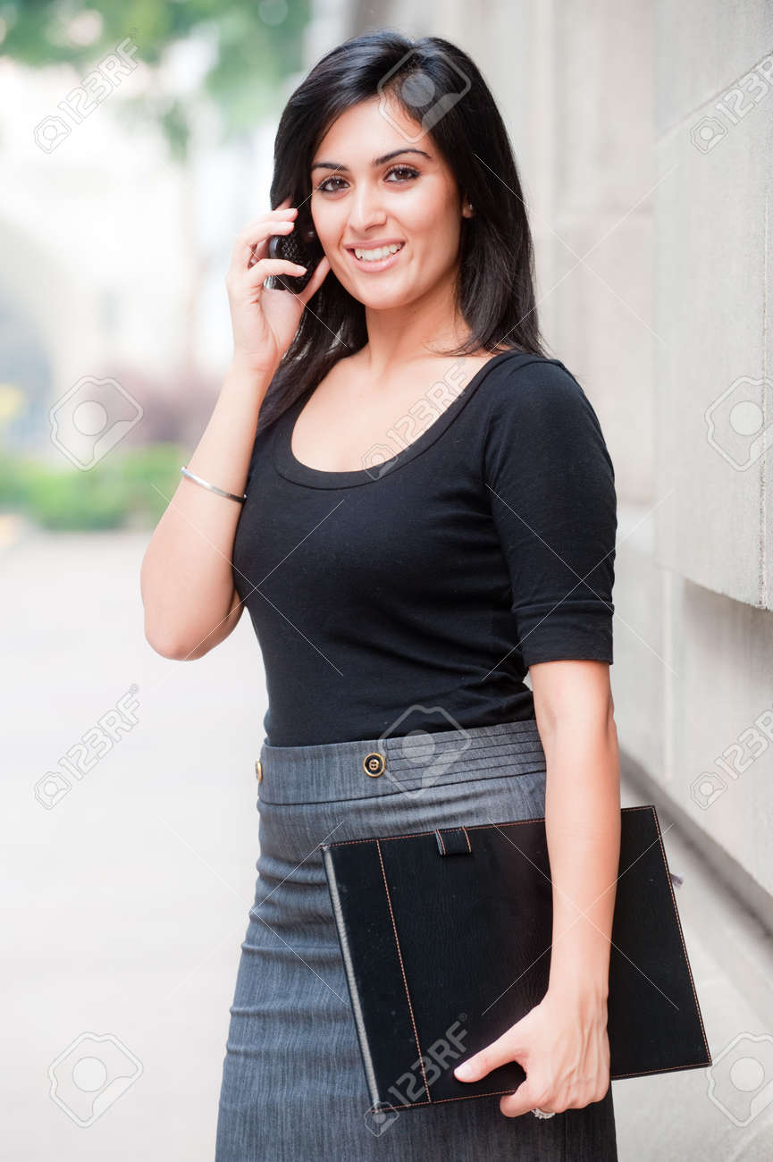 A young attractive Asian businesswoman standing outside with mobile phone Stock Photo - 8179092