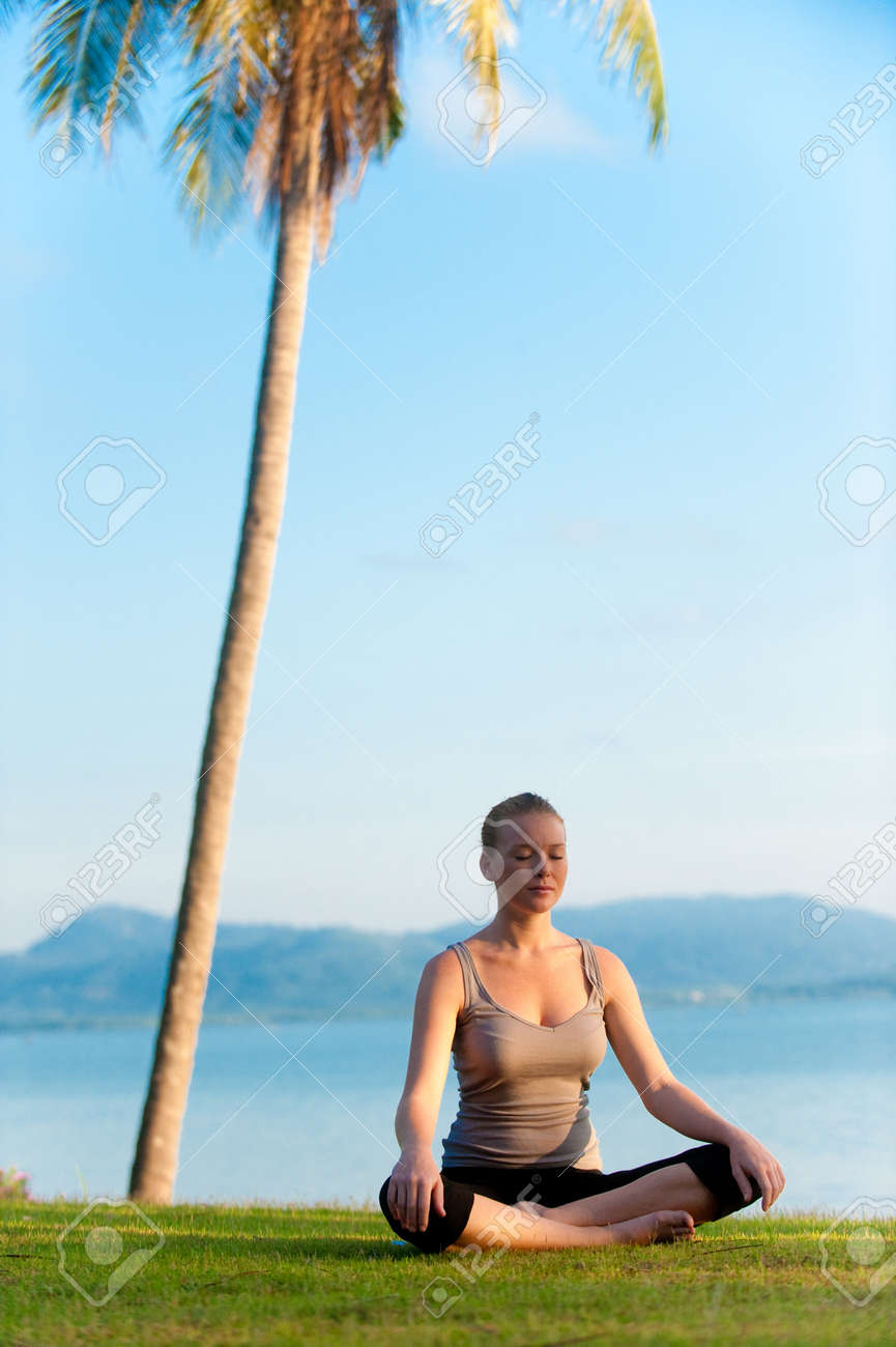 A young woman siting meditating as sun rises over tropical island setting Stock Photo - 9379838
