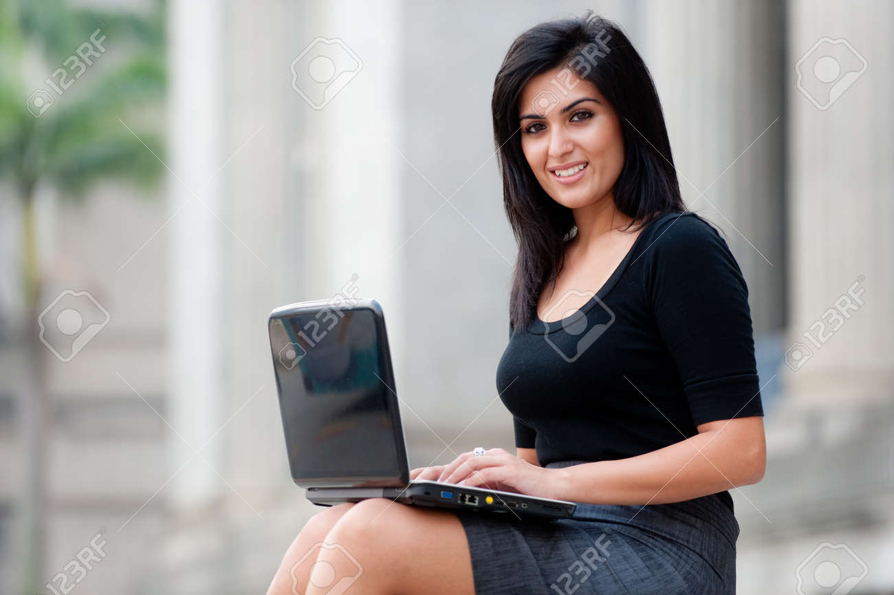 A young attractive Asian businesswoman sitting outside with laptop - 9379829
