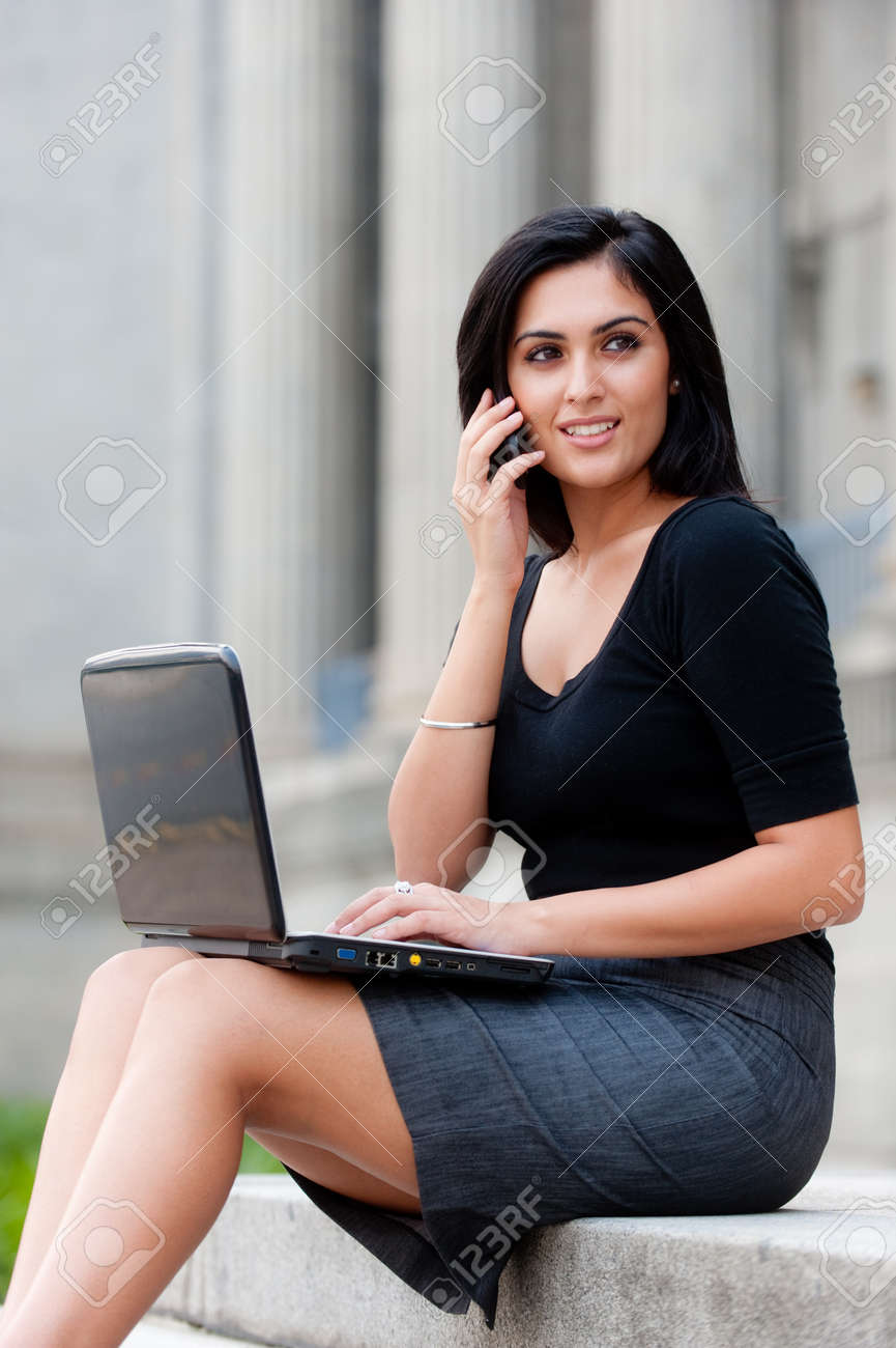 A young attractive Asian businesswoman sitting outside with laptop and phone Stock Photo - 9379839