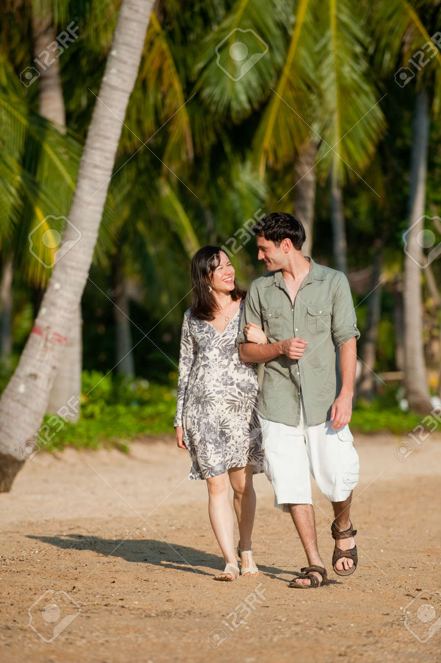 A young couple walking along a tree lined beach Stock Photo - 9404645