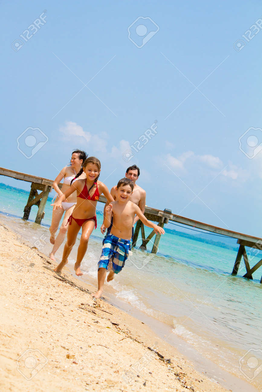 Young and attractive family of four enjoying themselves by the beach. Stock Photo - 9919191