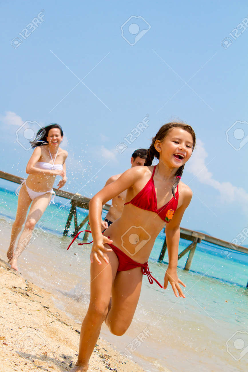Young and attractive family of three enjoying themselves by the beach. Stock Photo - 9919189