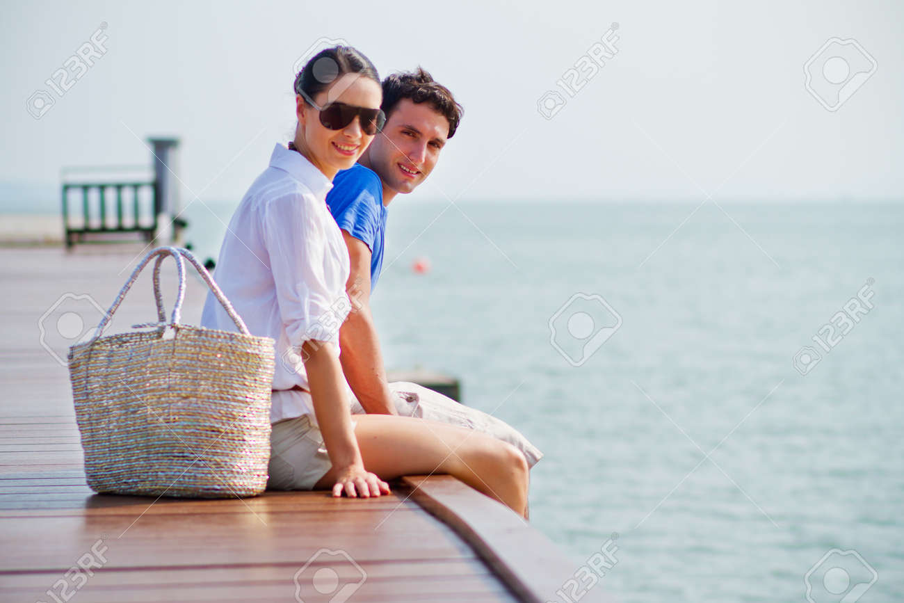 Side view of a couple sitting at the edge of a wooden boardwalk of a harbour Stock Photo - 10297178