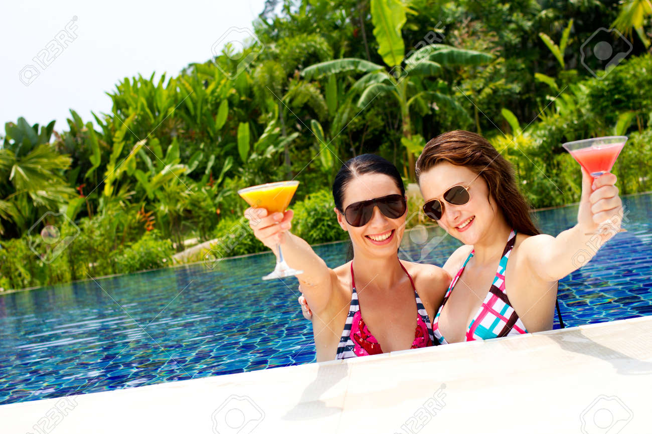 Two beautiful women enjoying their summer vacation with cocktails by the pool Stock Photo - 10307127