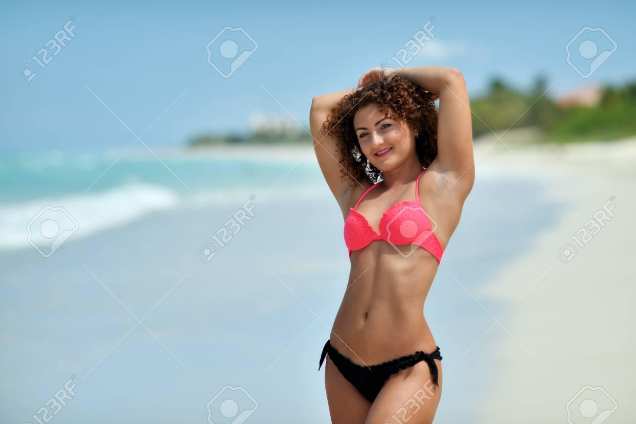 salvare b5b57 84321 Una ragazza giovane e riccia in un luminoso costume da bagno è in piedi  sulla spiaggia tropicale deserta