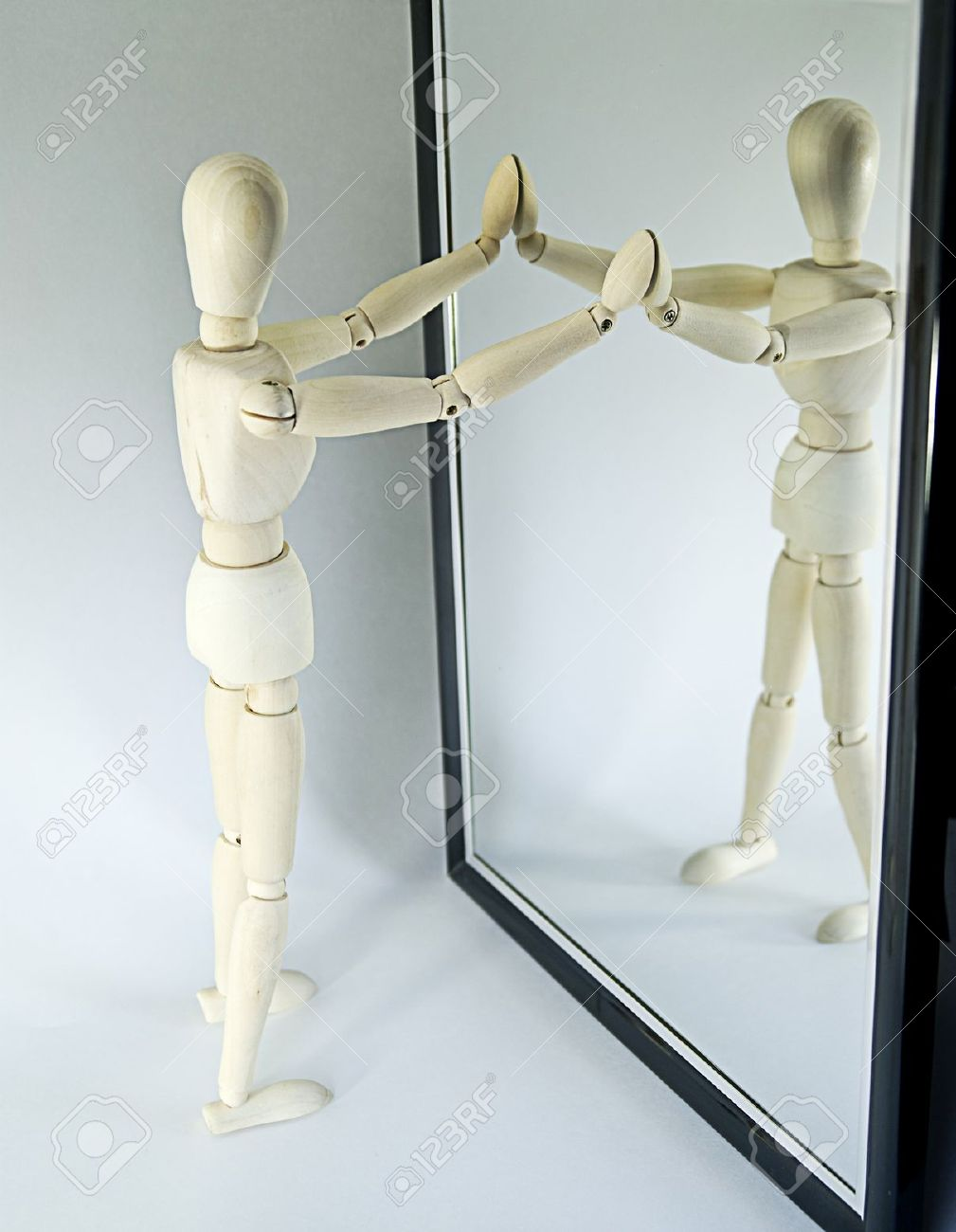 Closeup of wooden mannequin looking in full length mirror, white studio background. - 7334327