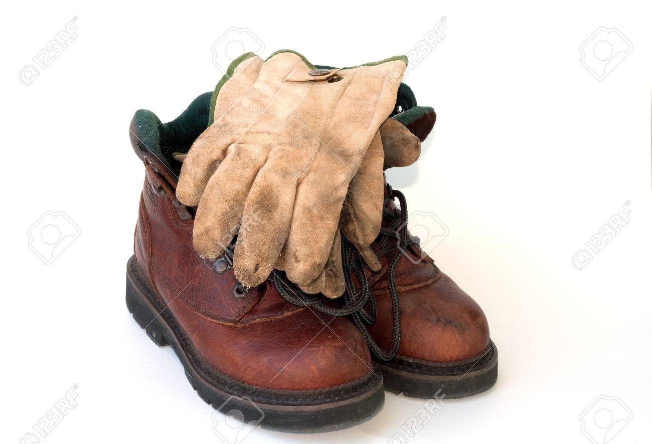 Work boots and well worn leather work gloves on a white background. Stock Photo - 10440493
