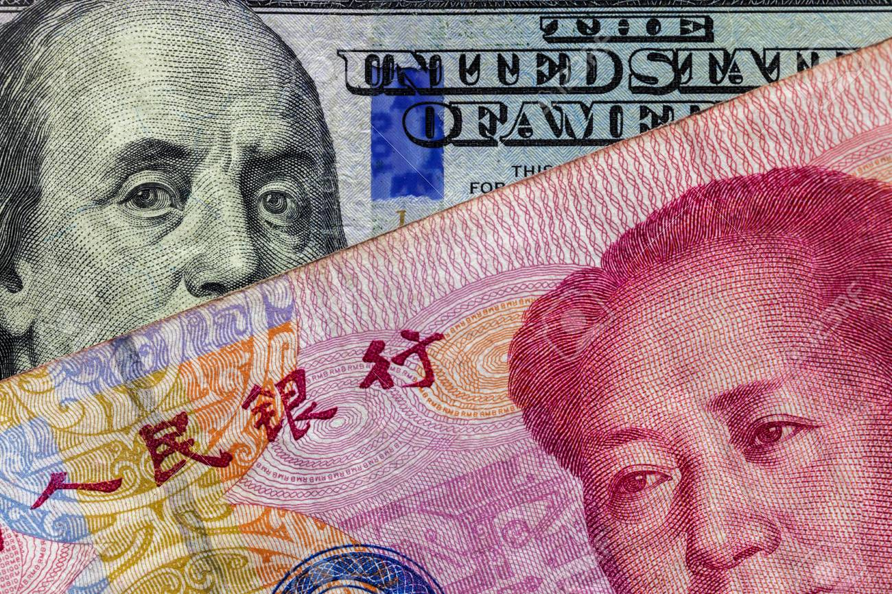 Close up of 100 Yuan banknote over a one hundred Dollar banknote with focus on portraits of Benjamin Franklin and Mao Tse-tung/USA vs China trade war concept - 99210037
