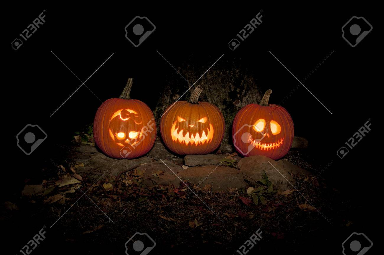 Three Jack O Lanterns Sit On The Ground Outdoors, Lighting The Night They
