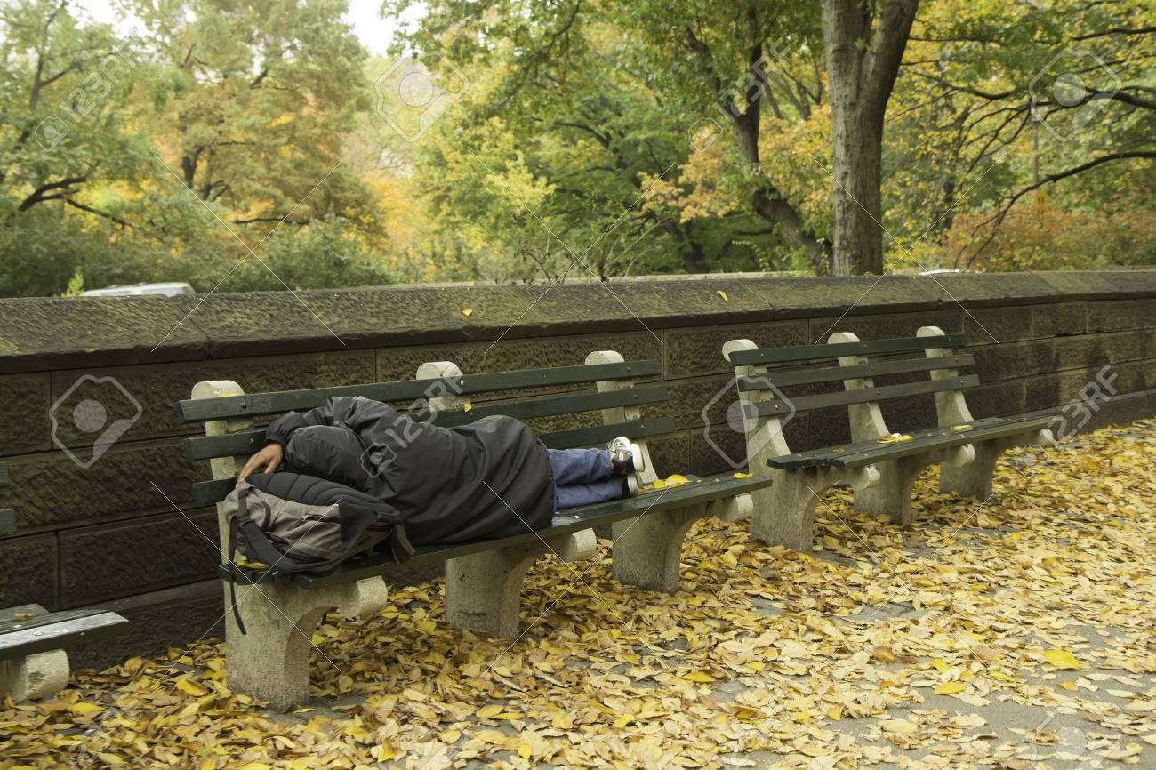 A Homeless Person Sleeps On A Park Bench Outside Of Central Park