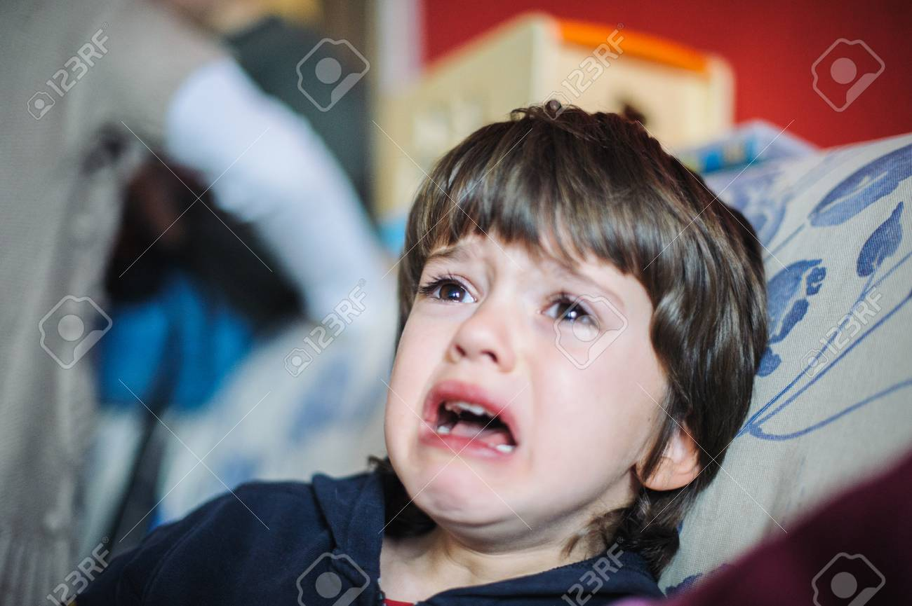 6 year old boy sad and crying in his home sitting on the couch stock photo