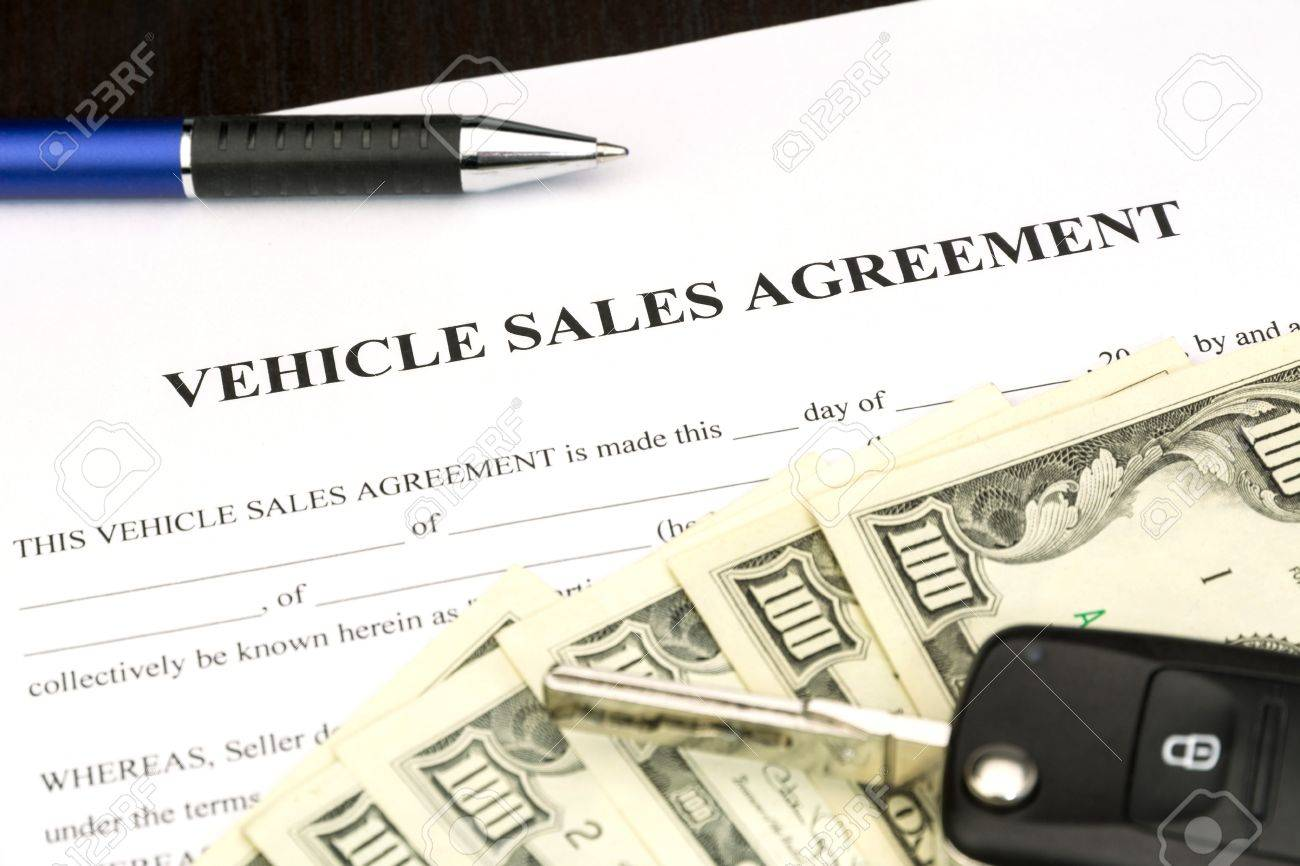 vehicle sales agreement document contract with car key and pen stock