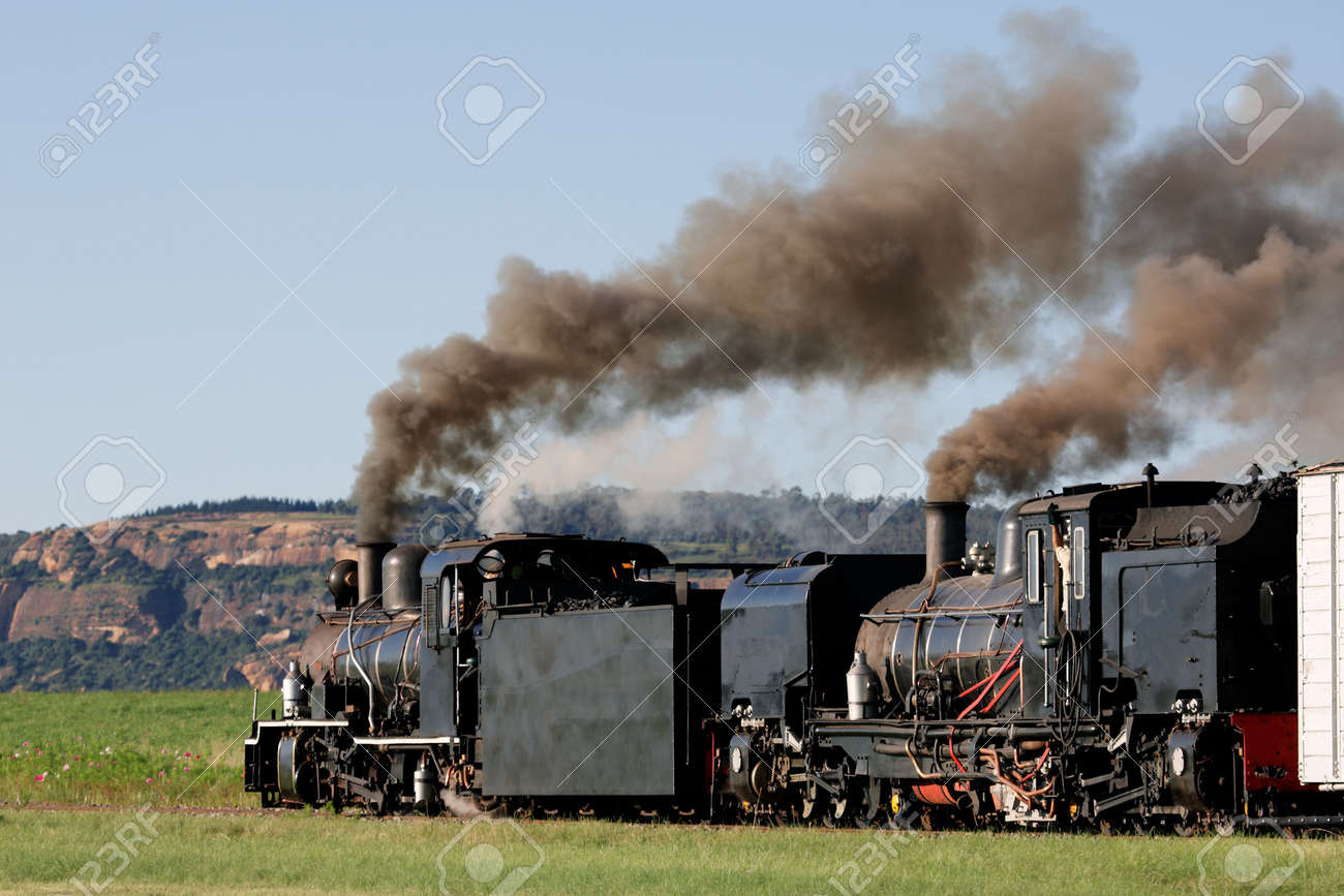 Two vintage steam locomotives with billowing smoke and steam Stock Photo - 4529948