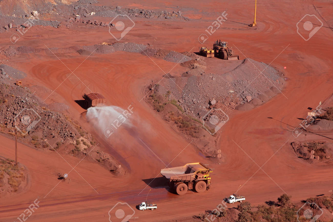 Large, open-pit iron ore mine with trucks - 12228887