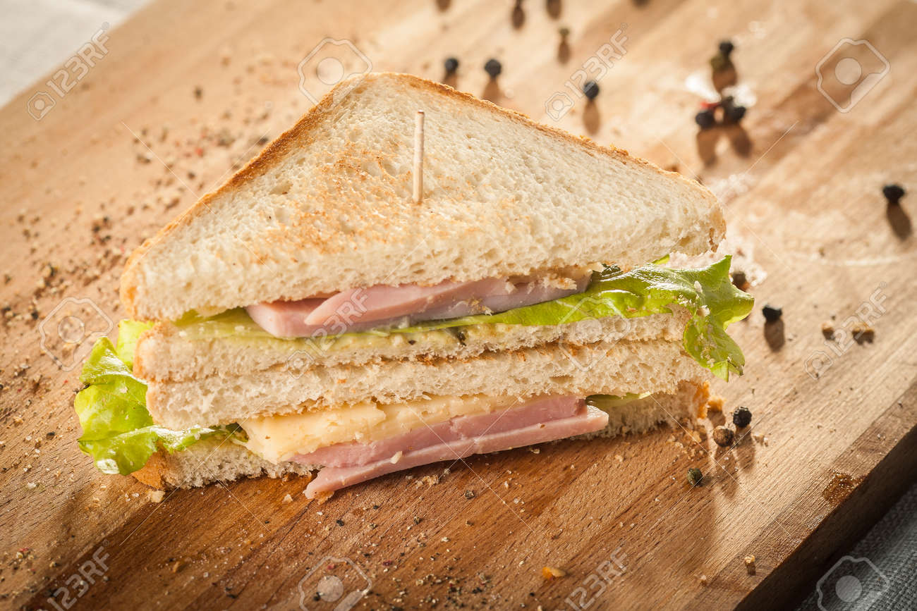 Cut by half sandwich with cheese, salad and ham. - 172306656
