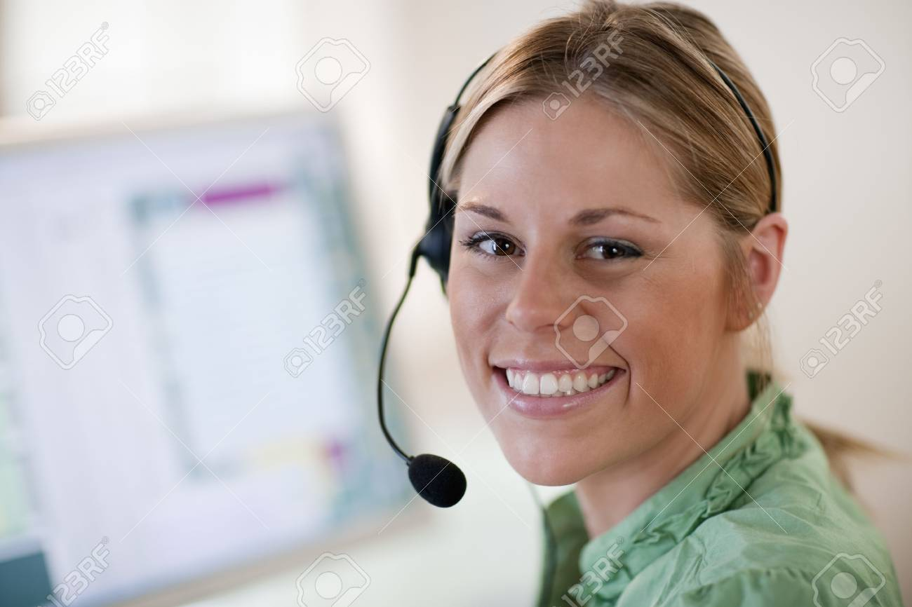 Close-up of a young woman in front of a computer, wearing a headset and smiling at the camera. Horizontal format. Stock Photo - 5840997
