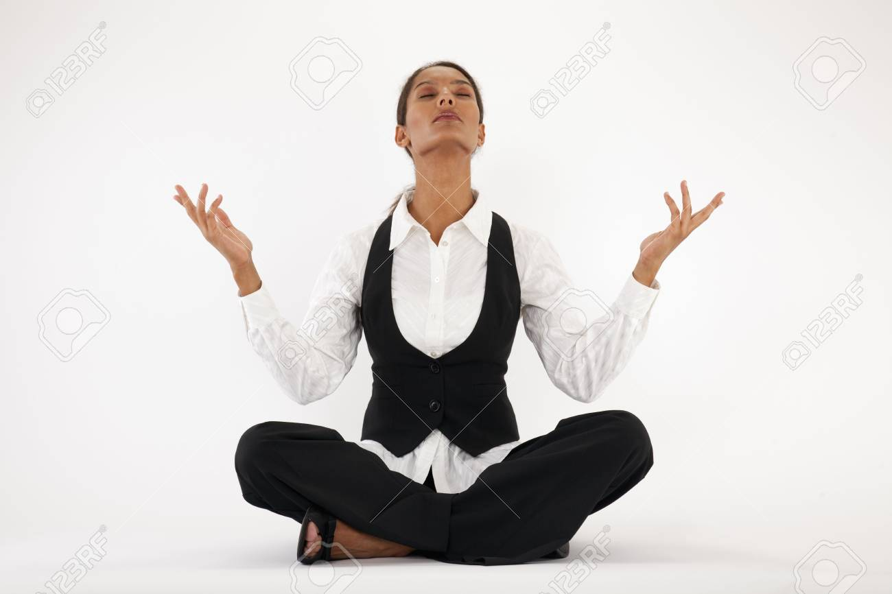 Young woman sitting cross legged and meditating. Horizontally framed shot. Stock Photo - 6043443